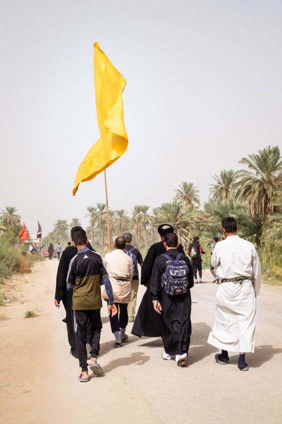Several pilgrims walking together on the road parallel to the river Euphrates in Al-Hilla toward Kerbala, Iraq