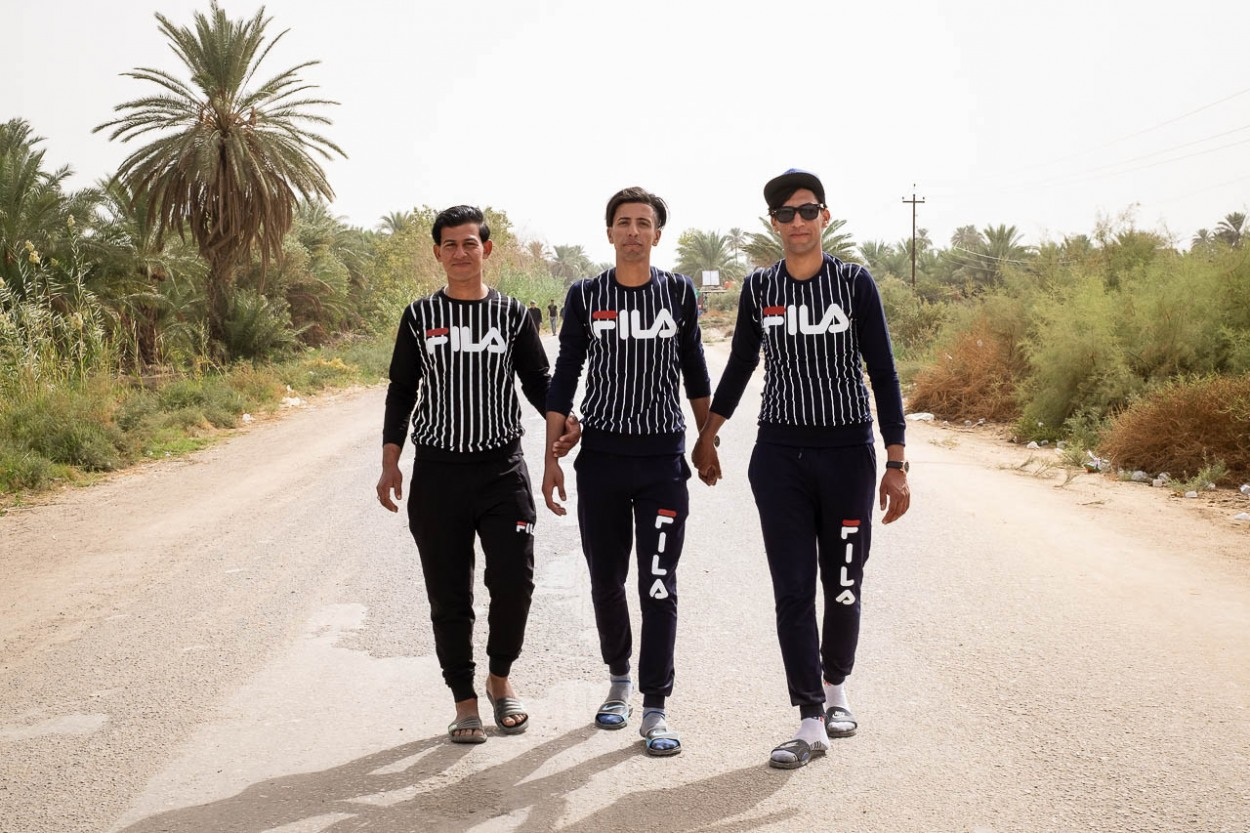 Three brothers, dressed in their finery, walk together on the road parallel to the Euphrates River in al-Hilla in the direction of Kerbala, Iraq
