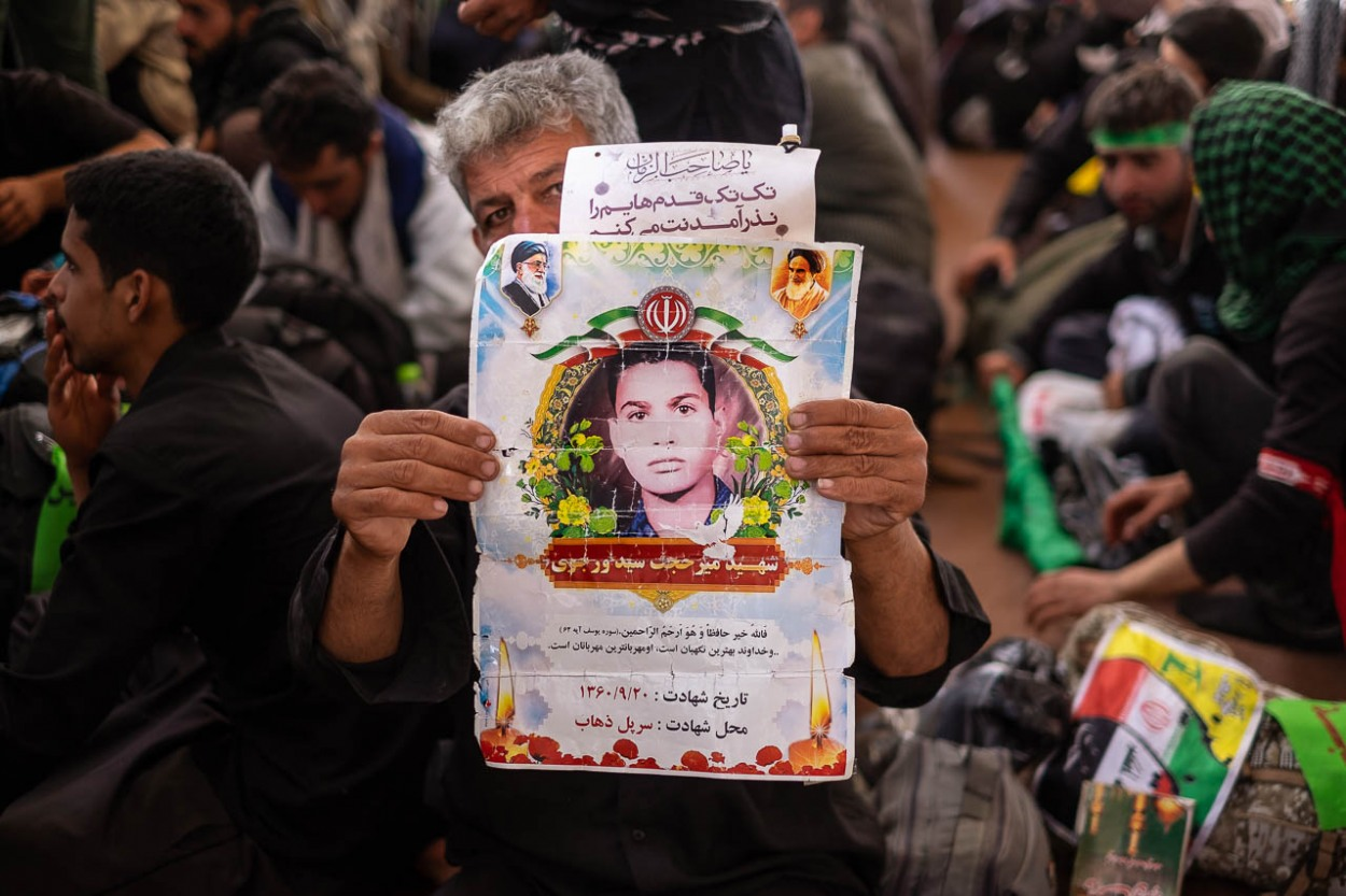 An Iranian pilgrim shows the image of his relative, martyred during the war between Iraq and Iran, the war imposed, as the Iranians usually call it.