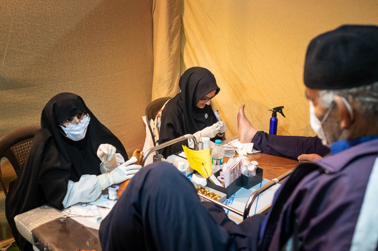 One of the most impressive facts about Arbaeen pilgrimage is to see how thousands of people help the pilgrims altruistically. In this case, two nurses treating the damaged feet of two pilgrims