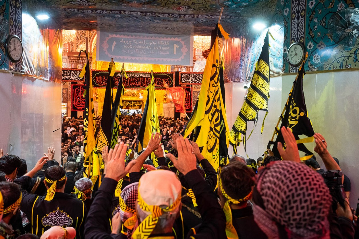 Brothers of Heyat Honar brotherhood express their devotion as they enter in the mausoleum of Imam Hussein in Karbala, Iraq