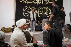 A young man consults and asks a sheikh for an advice in a mawakeb in al-Hilla, close to Karbala, Iraq